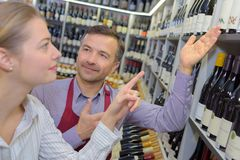 Handsome salesman advising wine to beautiful young customer. Handsome salesman is advising wine to a beautiful young customer Royalty Free Stock Images