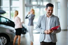 Handsome salesman at car dealership selling vehichles. Handsome young salesman at car dealership selling vehichles royalty free stock photography