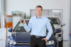 Handsome salesman holding key in car dealership. Handsome young salesman holding key in car dealership stock image