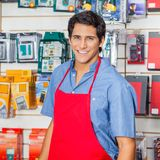 Handsome Salesman In Red Apron Smiling At Hardware Royalty Free Stock Images