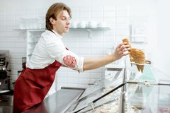 Salesman getting waffle cone for the ice cream in the shop. Handsome salesman taking waffle cone while making ice cream for the client in the modern pastry shop stock image