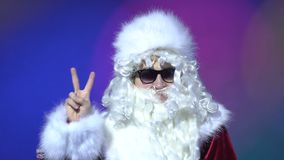 Handsome santa claus at night club doing victory sign with fingers to the camera. 4k stock video footage
