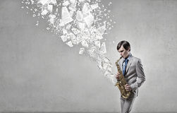 Handsome saxophonist. Concept image. Young man playing saxophone and papers coming out Stock Photography