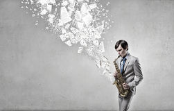 Handsome saxophonist. Concept image. Young man playing saxophone and papers coming out Royalty Free Stock Images