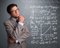 Handsome school boy thinking about complex mathematical signs. Handsome young school boy thinking about complex mathematical signs Royalty Free Stock Photography