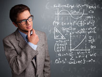 Handsome school boy thinking about complex mathematical signs Stock Photo