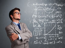 Handsome school boy thinking about complex mathematical signs Royalty Free Stock Image
