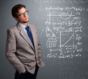 Handsome school boy thinking about complex mathematical signs Royalty Free Stock Photography