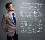 Handsome school boy thinking about complex mathematical signs Royalty Free Stock Photo