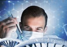 Young scientist mixing reagents in glass flask in clinical laboratory. Handsome scientist making research over dna molecule structure Royalty Free Stock Image