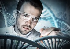 Young scientist mixing reagents in glass flask in clinical laboratory. Handsome scientist making research over dna molecule structure Royalty Free Stock Photos