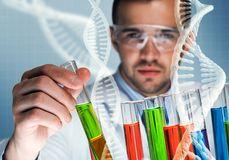 Young scientist mixing reagents in glass flask in clinical laboratory. Handsome scientist making research over dna molecule structure Stock Photos