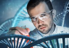 Young scientist mixing reagents in glass flask in clinical laboratory. Handsome scientist making research over dna molecule structure Stock Image