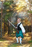Handsome scottish man with sword  in the forest Royalty Free Stock Image