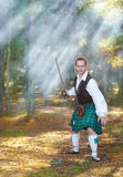 Handsome scottish man with sword  in the forest Royalty Free Stock Photography
