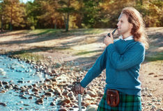 Handsome scottish man with sword and pipe Royalty Free Stock Photography