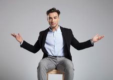 Handsome seated businessman making a welcoming hand gesture stock photo