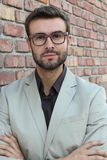 Handsome seductive man with glasses flirting and looking at camera with his arms crossed Royalty Free Stock Images