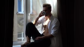 Handsome and seductive young man with naked torso drinks coffee sitting on the windowsill in the morning stock footage