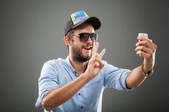 Handsome selfie man. Handsome man wearing hat making selfie, studio shot Royalty Free Stock Photo