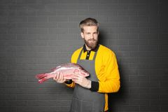 Handsome seller holding fresh fish. On gray wall background Stock Photos