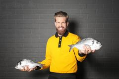 Handsome seller holding fresh fish. On gray wall background Royalty Free Stock Images