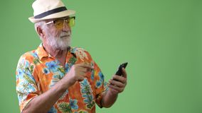 Handsome senior bearded tourist man ready for vacation against green background