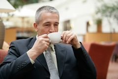 Handsome senior businessman wearing a suit drinking cup of coffee stock photos