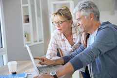 Handsome senior couple at home using laptop Stock Images