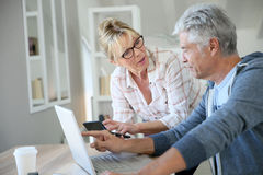 Handsome senior couple at home using smartphone and laptop Royalty Free Stock Image