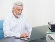 Senior doctor wearing in white uniform working with laptop. stock images