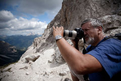 Handsome senior male photographer. In high mountain setting taking pictures Stock Photo