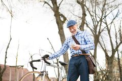 Senior man with smartphone and bicycle in town. Royalty Free Stock Photo