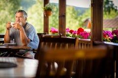 Handsome senior man enjoying his morning coffee Royalty Free Stock Image