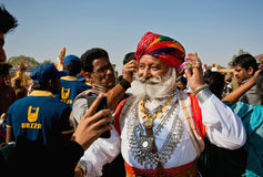 Handsome senior man with great mustaches in India. JAISALMER, INDIA: Handsome senior man with great mustaches in Rajput costume has fun in crowd of the Desert Stock Photography