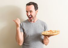 Handsome senior man at home. Senior man holding pizza pointing with hand and finger up with happy face smiling Stock Photos