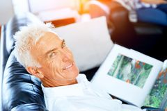 Handsome sennior man reading a book relaxing on a sofa. Handsome senior man reading book relaxing on a sofa in the living room at home stock images