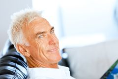 Handsome sennior man reading a book relaxing on a sofa. Handsome senior man reading book relaxing on a sofa in the living room at home stock photo