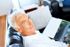 Handsome sennior man reading a book relaxing on a sofa. Handsome senior man reading book relaxing on a sofa in the living room at home royalty free stock images