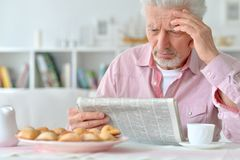 Senior man reading newspaper Stock Images