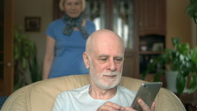 Handsome senior man sitting on chair at home. Using smartwatch, sending message, browsing, reading stock video footage