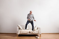 Handsome senior man standing on couch, dancing. Studio shot. Handsome senior man standing on couch, dancing, having fun. Studio shot against white wall Stock Photo