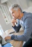 Handsome senior man thinking using laptop Stock Image
