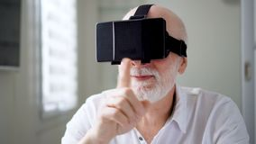 Handsome senior man in white using VR 360 glasses at home. Making browse, zoom and tap gestures stock video footage