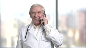 Handsome senior old doctor with stethoscope is talking on the mobile phone in hospital. Handsome senior old doctor in white coat and stethoscope is talking on stock video