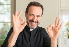 Handsome senior priest at home. Christian priest man doing ok sign with fingers, excellent symbol stock photo