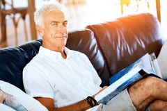 Handsome sennior man reading a book relaxing on a sofa. Handsome senior man reading book relaxing on a sofa in the living room at home royalty free stock photo