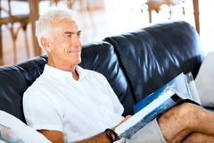 Handsome sennior man reading a book relaxing on a sofa. Handsome senior man reading book relaxing on a sofa in the living room at home stock image