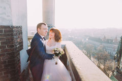 Handsome sensual groom hugging newlywed bride from behind at old castle balcony with city background Royalty Free Stock Photos