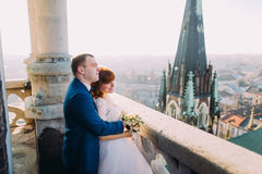 Handsome sensual groom hugging newlywed bride from behind at old castle balcony with city background Stock Photography
